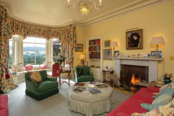 A colour image of the lounge with roaring fire at Edradynate Country House and Sporting Estate Scotland. Edradynate is available for rent, shoot days, fishing and family holidays on a catered or self catered basis.