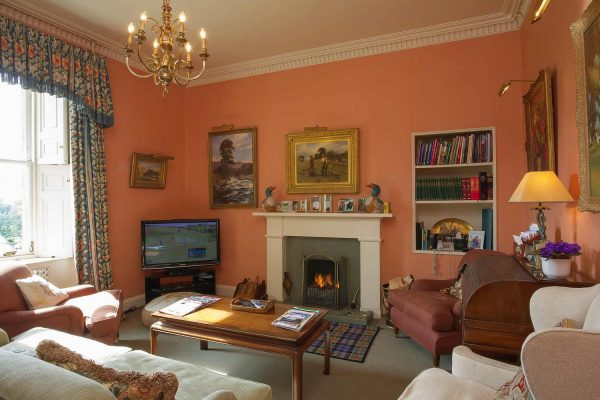 A colour image of the study with roaring fire at Edradynate Country House and Sporting Estate Scotland. Edradynate is available for rent, shoot days, fishing and family holidays on a catered or self catered basis.