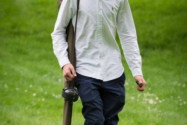 A COLOUR IMAGE OF A YOUNG GUEST WALKING AND CARRYING A GUN AT EDRADYNATE ESTATE clay pigeon shoot day - Edradynate Estate, Perthshire - Luxury Country House and Sporting Estate for Rent in Scotland