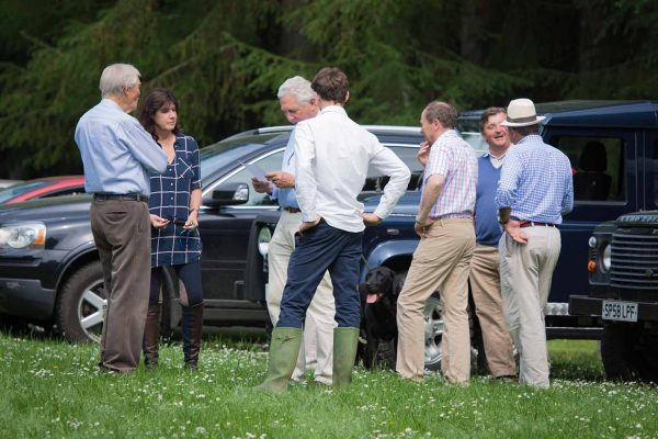 A colour image of Michael Campbell stood with guests socialising stood by 4 x 4 vehicles at the Edradynate May 2017 clay pigeon shoot day - Edradynate Estate, Perthshire - Luxury Country House and Sporting Estate for Rent in Scotland